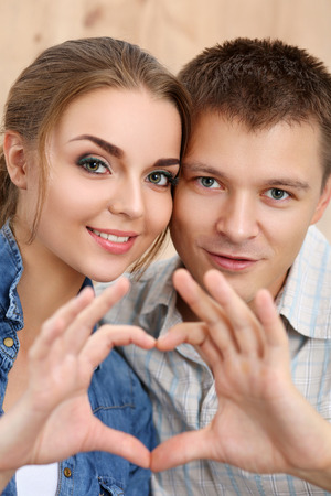 heart in hand: Portrait of smiling beautiful girl and her boyfriend making shape of heart by their hands. Love concept. Stock Photo