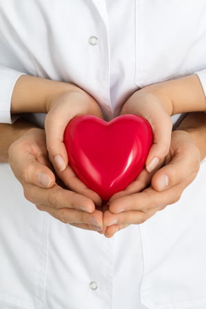 Womans and mans hands holding red heart together. Love, assistance and healthcare concept. Stock Photo