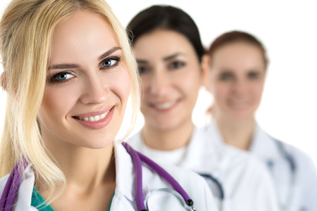 doctor female: Portrait of young blonde female doctor surrounded by medical team, looking at camera and smiling. Healthcare and medicine concept.