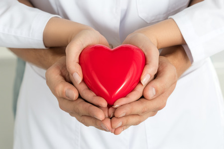 healthcare and medicine: Womans and mans hands holding red heart together. Love, assistance and healthcare concept Stock Photo