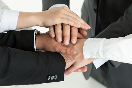 empleados trabajando: Primer plano de equipo de negocios que muestra la unidad con poner sus manos en la parte superior de uno al otro. Concepto de trabajo en equipo.