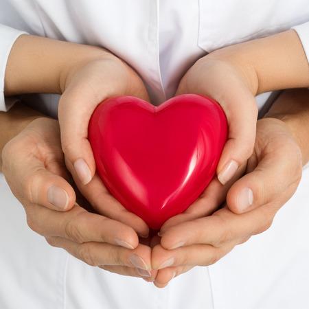 vida saludable: La mujer y el hombre con corazón rojo juntos en sus manos. El amor, la asistencia y el concepto de salud Foto de archivo