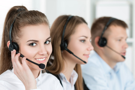 business support: Portrait of call center worker accompanied by her team. Smiling customer support operator at work. Help and support concept