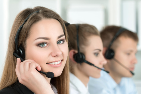 handsfree telephones: Portrait of call center worker accompanied by her team. Smiling customer support operator at work. Help and support concept