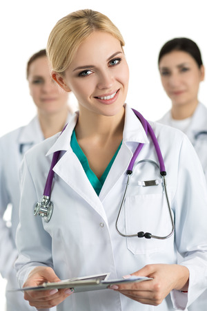 healthcare portrait: Portrait of young blonde female doctor holding file with documents surrounded by medical team, looking at camera and smiling. Healthcare and medicine concept.