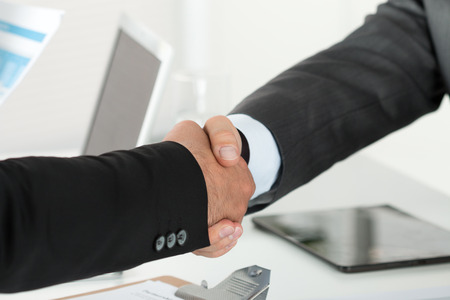 human relationships: Business handshake. Two businessman shaking hands with each other in the office.