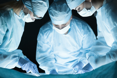 surgeons hat: Medical team performing operation. Group of surgeon at work in operating theatre toned in blue