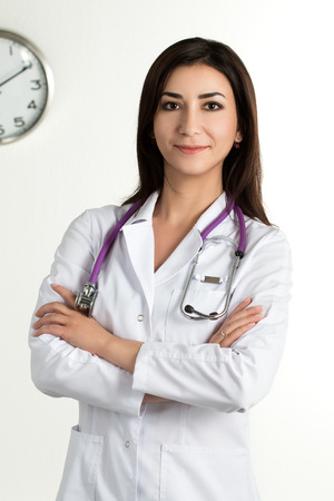 medical services: Beautiful smiling female medicine doctor standing with folded hands. Healthcare and medicine concept