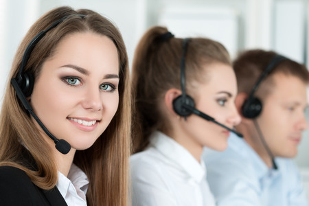 business centre: Portrait of call center worker accompanied by her team. Smiling customer support operator at work. Help and support concept