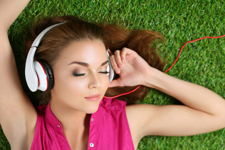 listening: Young beautiful girl laying on the grass in park listening to music. Summertime and leisure concept. Top view. Copyspace.