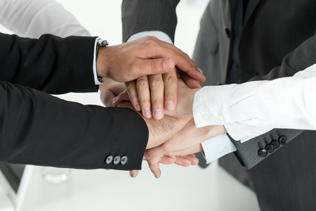 work: Closeup of business team showing unity with putting their hands together on top of each other. Concept of teamwork.