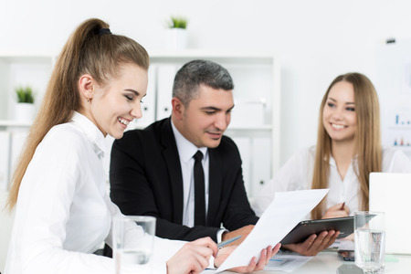 businesswoman suit: Two young beautiful business women consulting with their colleague. Partners discussing documents and ideas Stock Photo