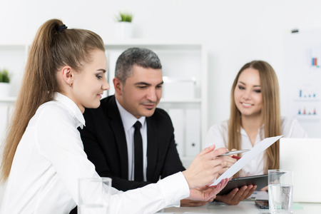 consulting business: Two young beautiful business women consulting with their colleague. Partners discussing documents and ideas Stock Photo
