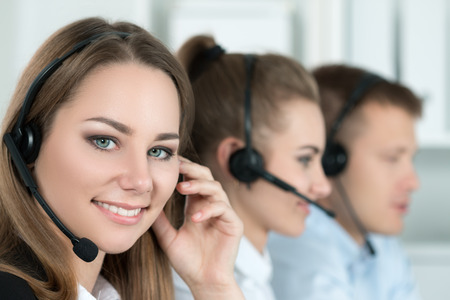 on call: Portrait of call center worker accompanied by her team. Smiling customer support operator at work. Help and support concept