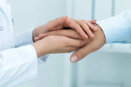 reassure: Female medicine doctor reassuring her patient. Hands close-up. Healthcare and medical concept. Stock Photo