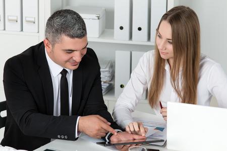 planificacion: Joven y bella mujer de negocios de consultar con su colega masculino que muestra algo en tablet PC. Socios de examinar los documentos e ideas