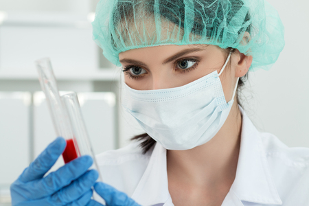Medical doctor in protective gloves and surgical mask and hat comparing two flasks with dark red liquid in laboratory. Scientific research, healthcare and medical concept.