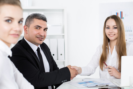 handclasp: Businessman in suit shaking young business womans hand. Partners made deal and sealed it with handclasp. Formal greeting gesture Stock Photo