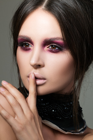 aristocrat: Close-up portrait of beautiful brunette woman with modern fashion make up making shh sign with her finger. Beauty, secrecy and fashion concept.