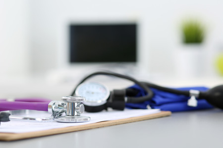 office life: Medicine doctors working place. Stethoscope and manometer lying on table at physicians office. Healthcare, health life and medical concept