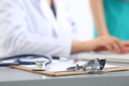 De werkplaats van de arts van de geneeskunde. Focus op stethoscoop, doctor's handen iets te typen op de achtergrond. Gezondheidszorg en medisch concept. copyspace