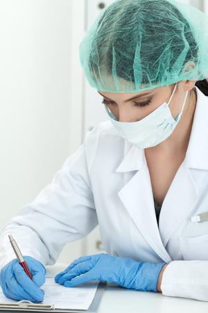 bata blanca: doctor en medicina en guantes de protección, mascarilla quirúrgica y la escritura sombrero de algo. La investigación científica, la salud y el concepto médico. Foto de archivo