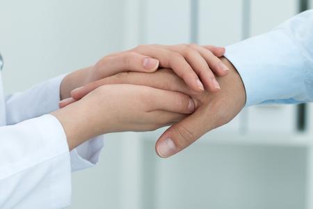 Vrouwelijke geneeskunde arts geruststellend haar patiënt. Handen close-up. Gezondheidszorg en medische concept.