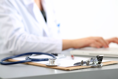 Medicine doctor's working place. Focus on stethoscope, doctor's hands typing something on background. Healthcare and medical concept. Copyspace Stockfoto