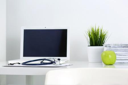 estetoscopio: Mesa de trabajo Medicina del doctor. Ordenador port�til, papeles, verde manzana y un estetoscopio mentir sobre la mesa en la oficina del m�dico. Salud y concepto m�dico