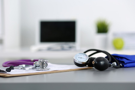 healthcare professional: Medicine doctors working place. Stethoscope and manometer lying on table at physicians office. Healthcare and medical concept Stock Photo