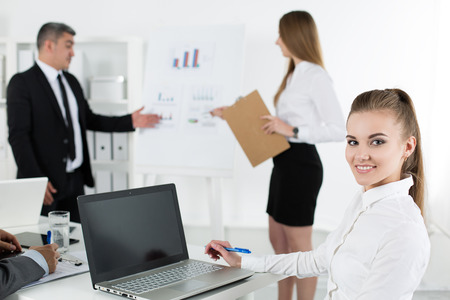 business management: Business people meeting in office to discuss project. Young pretty female office worker looking at camera with her colleagues acting on background. Business meeting and teamwork concept