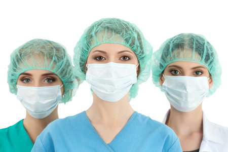 Young woman doctor in cap and face mask with two her collegues standing behind her. Healthcare, medical, surgery and team work concept Banque d'images