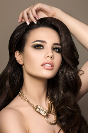 Beauty portrait of young pretty brunette girl wearing golden necklace and touching her hair