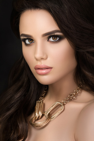 woman face close up: Beauty portrait of young pretty brunette girl wearing golden necklace Stock Photo