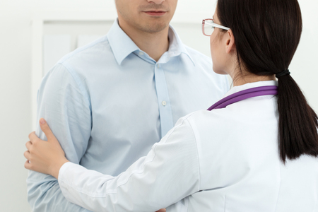 hand in hand: Friendly female doctor touching male patients arm for encouragement and empathy. Partnership, trust and medical ethics concept. Bad news lessening and support. Patient cheering and support Stock Photo