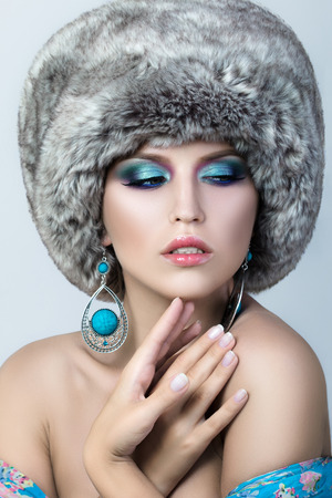 pretty young girl: Beauty portrait of young pretty lady wearing fur cap and blue earrings. Winter fashion make up