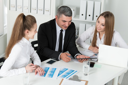 consulting business: Adult businessman consulting his young female colleagues during business meeting. Partners discussing documents and ideas