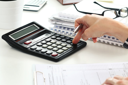 tax: Close up of female accountant or banker making calculations. Savings, finances and economy concept
