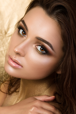 Beauty portrait of young pretty woman with fashion make-up. Bronzed skin and golden smokey eyes.