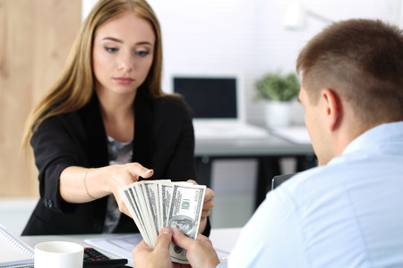 Vrouw nemen partij van honderd dollarbiljetten. Omkoopbaarheid, omkoping, corruptie begrip