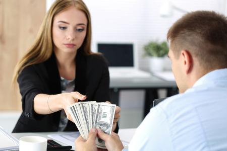 venality: Woman taking batch of hundred dollar bills. Venality, bribe, corruption concept