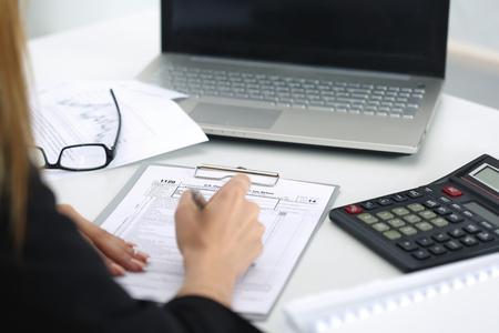 impuestos: Cierre de tiro de formulario de impuestos de llenado mano de la mujer. Ahorros, finanzas y economía de concepto