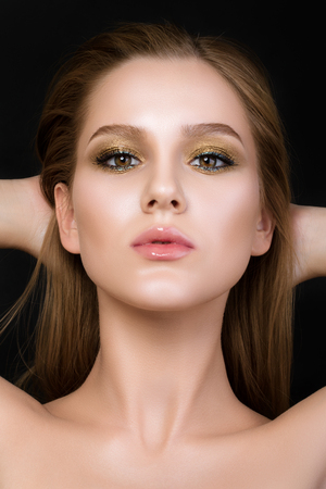 fashion girl: Beauty portrait of young woman with beautiful make-up. Golden smokey eyes.