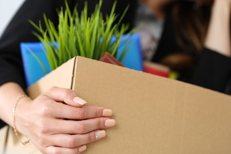 unemployed dismissed: Young dismissed female worker in office holding carton box with her belongings Stock Photo