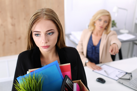 woman boss: Boss dismissing an employee. Dejected fired office worker carrying a box full of belongings.