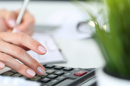 Woman hands working on calculator close up