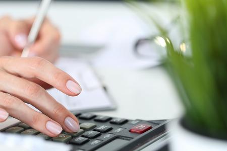 impuestos: Manos de la mujer que trabaja en calculadora cerca Foto de archivo