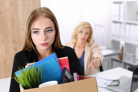 employment issues: Boss dismissing an employee. Dejected fired office worker carrying a box full of belongings.