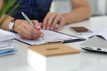 Close-up der weiblichen Händen. Woman Writting etwas und schaut auf Handy-Bildschirm sitzt in ihrem Büro