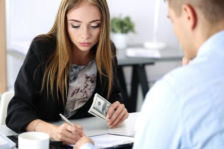 fraud: Woman signing documents after reseiving a batch of handred dollar bills. Venality, bribe, corruption concept Stock Photo
